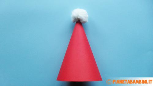 Applicazione del pon pon al cappello di Babbo Natale