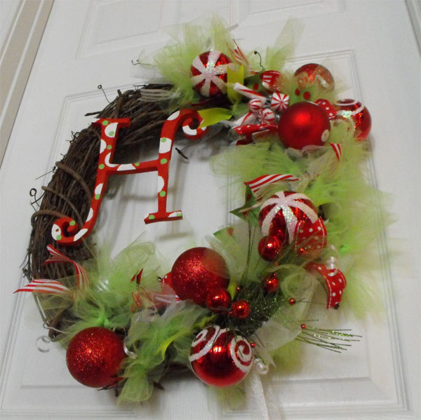 Ghirlanda natalizia intrecciata con rametti, palline rosse e stoffa voile