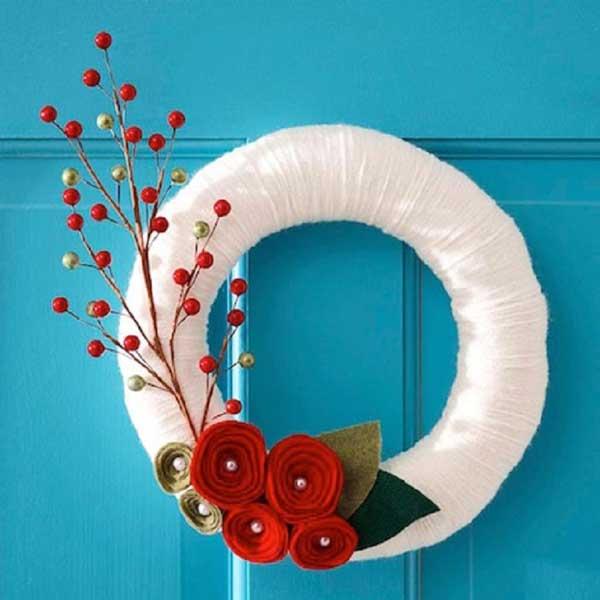 Ghirlanda natalizia con stoffa intrecciata e rametto decorativo