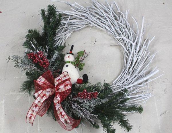 Ghirlanda natalizia con rametti di pino e pupazzo di neve