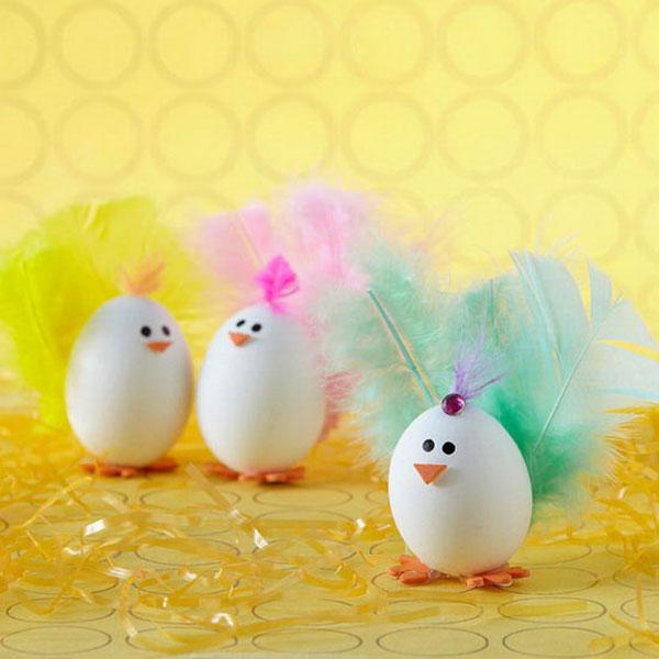 Uova di Pasqua decorate a forma di pulcini con code colorate