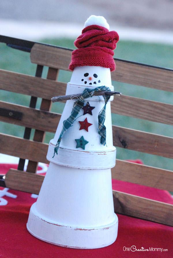 Pupazzo di neve creato con vasi di terracotta e decorazioni