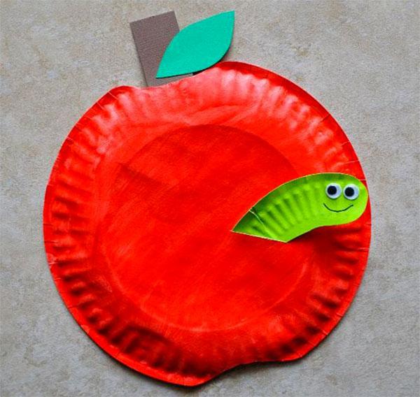 Mela con verme creato con piatti di plastica