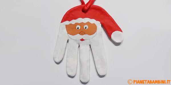 Viso di Babbo Natale creato con la pasta di sale sull'impronta di una mano