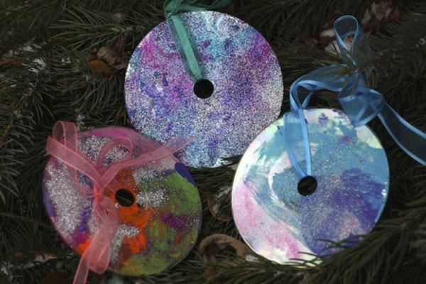 Decorazioni natalizie create con CD usati e glitter per bambini
