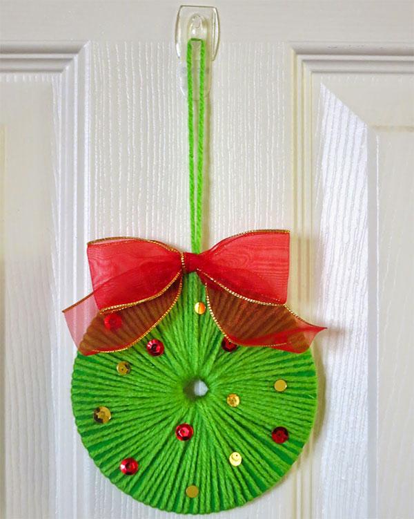 Decorazione natalizia creata con CD usati e lana per bambini