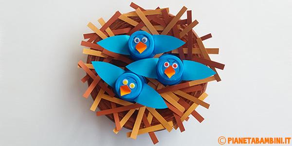 Uccellini nel nido con piatto e bicchieri di plastica come lavoretto di primavera