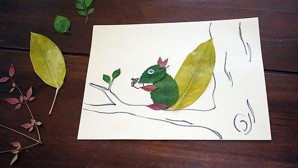 Lavoretto d'autunno scoiattolo con foglie autunnali